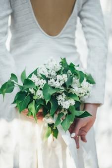 Un ramo de lilas blancas en manos de la novia.