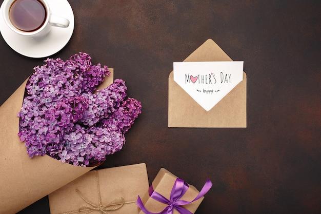 Un ramo de lilas con una taza de té, caja de regalo, sobre de artesanía, una nota de amor sobre fondo oxidado. día de la madre