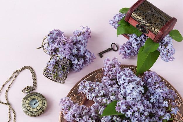 Un ramo de lilas en una vieja placa de bronce, una pequeña jaula de bronce, un reloj viejo de bolsillo.