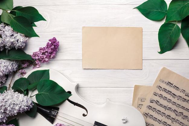 Un ramo de lilas con violín, letra y hoja de música en una mesa de madera blanca. top wiev con espacio para tu texto