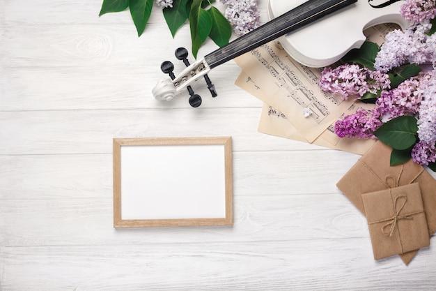 Un ramo de lilas con violín, pizarra y música sobre una mesa de madera blanca. top wiev con espacio para tu texto