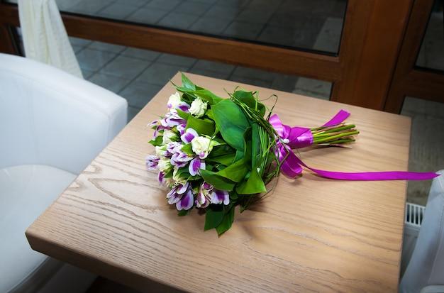 Ramo de lirios morados sobre mesa de madera