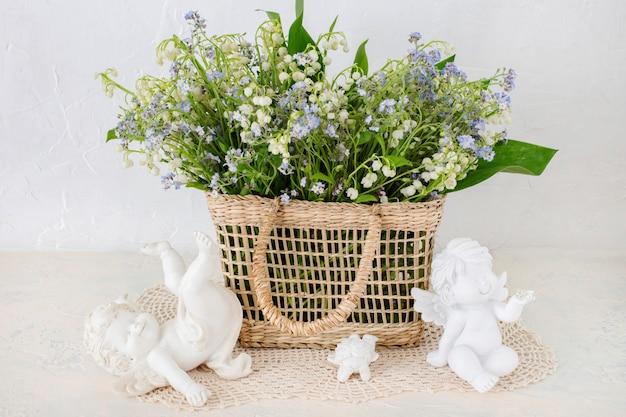 Un ramo de lirios del valle y no me olvides en una cesta sobre la mesa y tres ángeles.