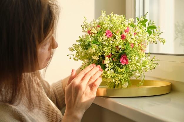 Ramo de lirios del valle rosas de plantas verdes en mano de mujer, primer plano