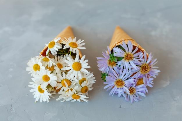 Ramo de manzanillas en un cono de waffle sobre un fondo gris. las flores están floreciendo. flores silvestres