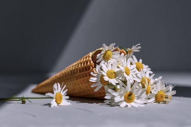 Ramo de manzanillas en un cono de waffle sobre un fondo gris. helado de manzanilla. las flores están floreciendo. flores silvestres