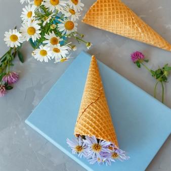 Ramo de manzanillas en un cono de waffle sobre un fondo gris y libro azul. las flores están floreciendo. flores silvestres