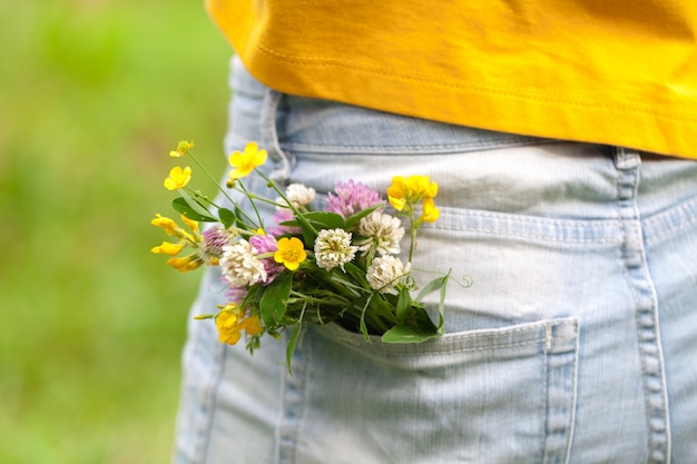 Ramo de margaritas en el bolsillo de jean