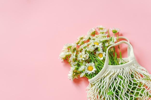 Ramo de margaritas de campo en compras reutilizables bolsa de malla ecológica sobre fondo rosa.