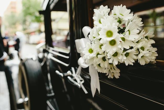 Ramo de margaritas que adornan un coche antiguo de la boda.