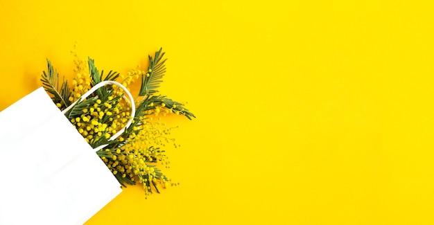 Un ramo de mimosa en una bolsa de regalo blanca. compras de primavera