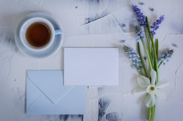 Ramo muscari con tarjeta y taza de té en madera
