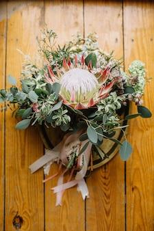 Ramo de novia de boda con flor de protea y ramas de eucalipto en bandeja vintage en madera