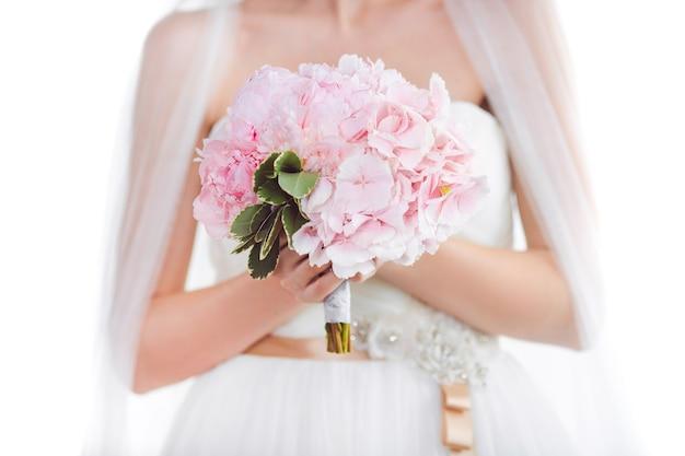 Ramo de novia hermoso de flores rosas de la boda en manos de la novia