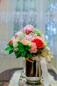 Ramo de novia con orquídeas blancas, margaritas y frutos rojos.