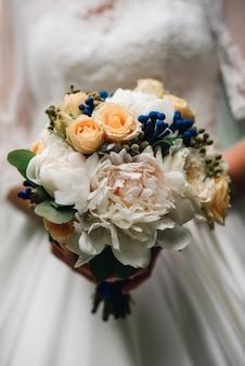 Ramo de novia de peonías blancas y rosas en las manos