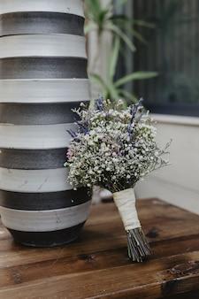 Ramo de novia con pequeñas flores blancas y moradas junto a un jarrón a rayas