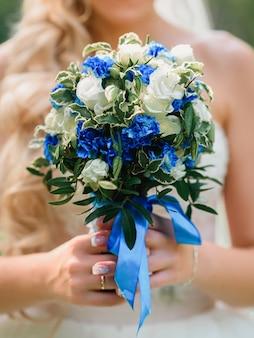 Ramo de novia con rosas blancas y flores azules en las manos