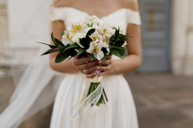 Ramo de novia con rosas blancas y hojas verdes. la novia vestida tiene ramo.