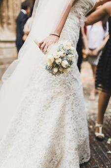 Ramo de novia sostenido por ella con sus manos en su boda