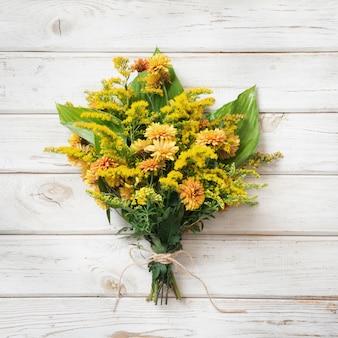 Ramo otoñal de flores silvestres amarillas sobre tabla de madera blanca.