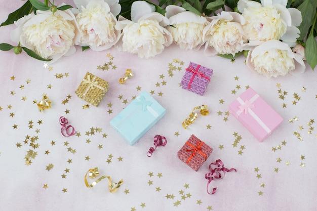 Un ramo de peonías blancas, regalos y decoración festiva.