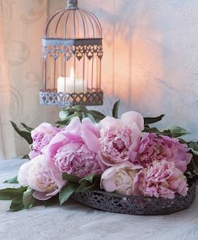 Un ramo de peonías rosas sobre una mesa de madera en un jarrón antiguo y una vela en una jaula decorativa