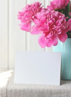 Ramo de peonías rosas y una tarjeta vacía. flores de jardín en un jarrón de vidrio. maqueta, creador de escenas.
