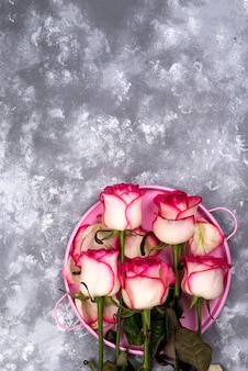 Ramo rojo de la flor de la rosa del blanco con la caja de regalo rosada en la tabla de piedra.