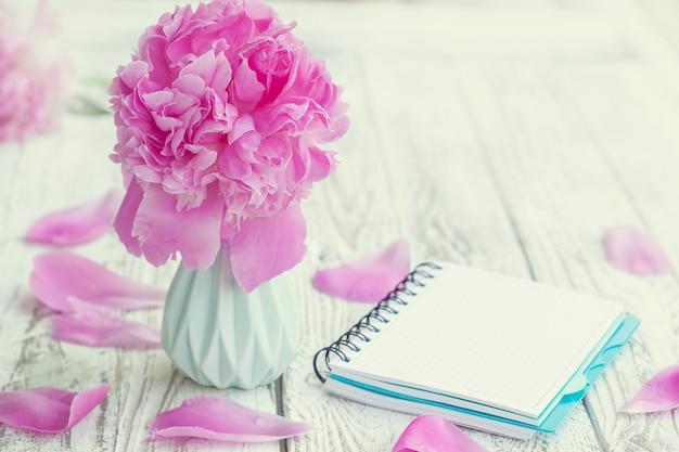 Ramo rosado pálido hermoso de las peonías en florero y cuaderno vacío sobre el fondo blanco de la tabla.