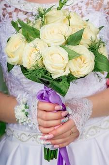 Ramo de rosas amarillas claras en manos de la novia.