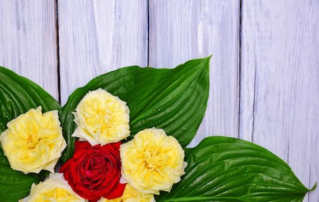 Ramo de rosas amarillas y rojas con hojas verdes.