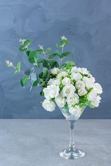 Ramo de rosas blancas con hojas verdes en copa de cóctel de vidrio