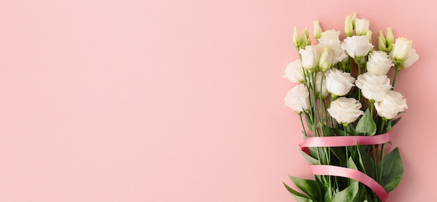 Ramo de rosas blancas con lazo rosa.