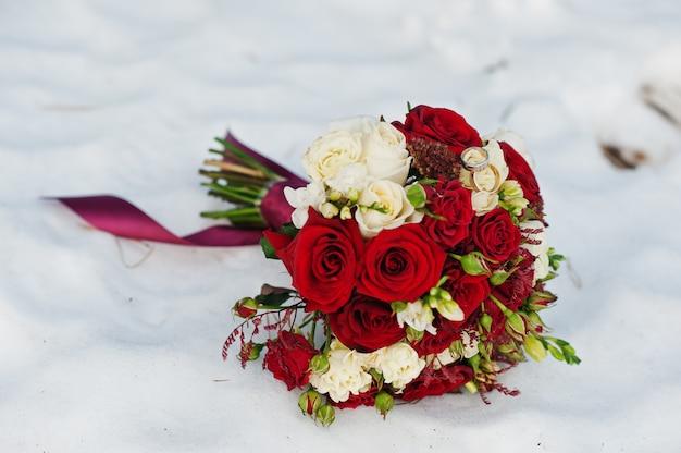 Ramo de rosas blancas y rojas en la nieve.