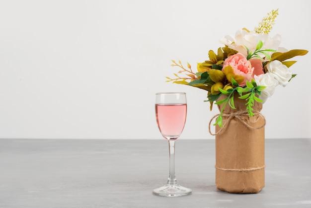 Ramo de rosas blancas y rosadas y copa de vino rosado en mesa gris