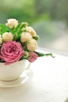 Ramo de rosas blancas en una taza sobre una mesa blanca frente a la ventana
