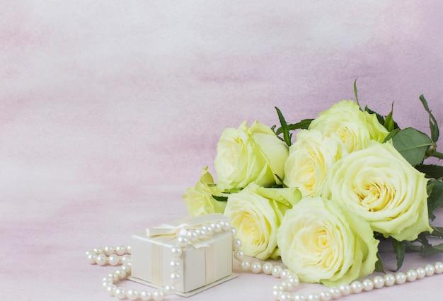 Ramo de rosas claras, caja de regalo y cuentas de perlas sobre un fondo rosa