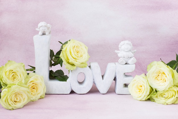Ramo de rosas claras y la palabra amor de piedra y dos figuras de ángeles.