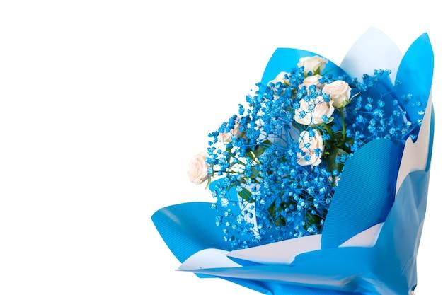 Ramo de rosas claras y pequeñas flores azules aisladas sobre una superficie blanca