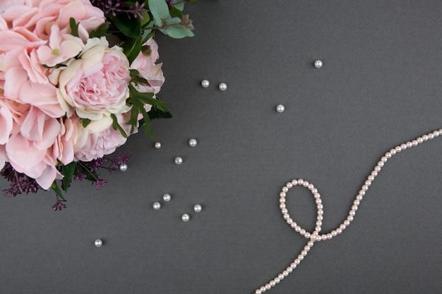 Ramo de rosas con collar de perlas sobre fondo gris