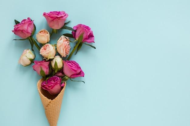 Ramo de rosas envuelto en cono de helado con copia espacio de fondo