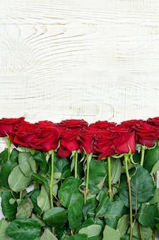 Ramo de rosas escarlatas sobre un fondo claro de la madera. de cerca