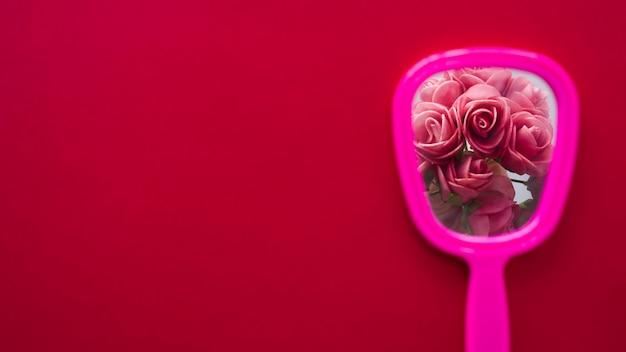 Ramo de rosas en espejo en mesa.