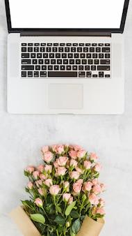 Ramo de rosas frente a una computadora portátil abierta con pantalla en blanco en blanco