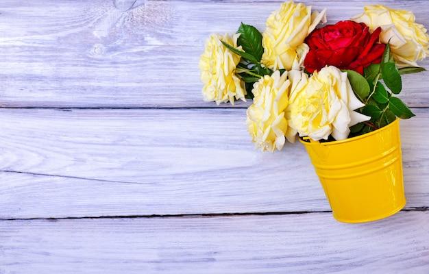 Ramo de rosas frescas en un cubo de hierro amarillo