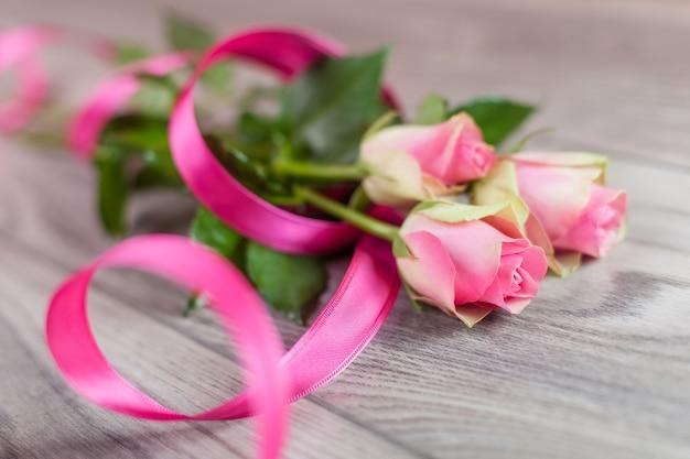 Ramo de rosas frescas sobre madera