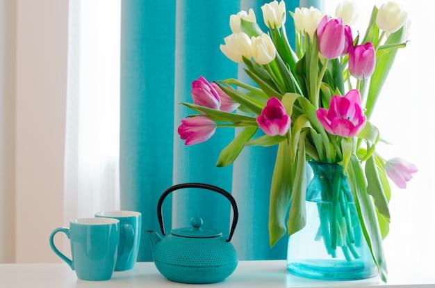 Ramo de rosas hermosas y tulipanes en jarrón tiffany, taza, platillo y tetera.