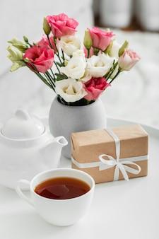 Ramo de rosas en un jarrón junto a un regalo envuelto