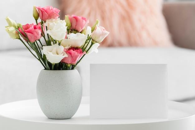 Ramo de rosas en un jarrón junto a la tarjeta vacía